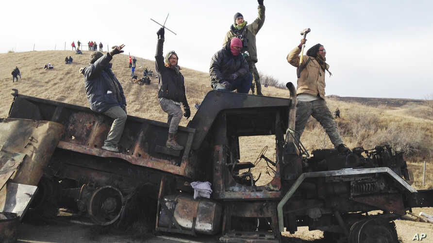 FILE - Protesters against the Dakota Access oil pipeline stand on a burned-out truck near Cannon Ball, N.D., that they removed from a long-closed bridge near their camp in North Dakota, Monday, Nov. 21, 2016.