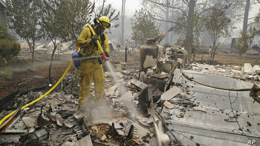 A firefighter with the Montezuma Fire District puts out hot spots at a home destroyed by fire Sunday, Sept. 13, 2015, in Middletown, California.