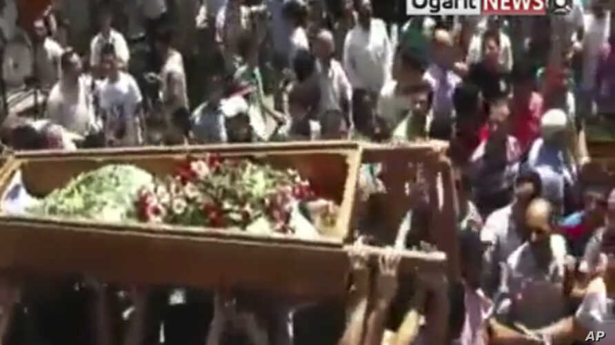 Mourners carry the body of a person during a funeral ceremony in the city of Homs, Syria in this image made from amateur video released by Ugarit News, Aug. 2, 2011