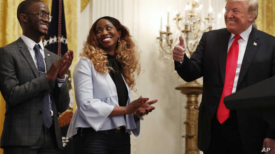 President Donald Trump, right, makes the thumbs up sign toward Cam'eron Hill, left, and his mother LaSonya Hill, of Jacksonville, Fla., during an event about taxes, June 29, 2018, in the East Room of the White House in Washington.