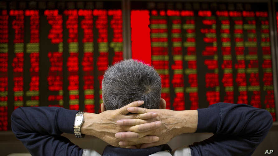 FILE - A Chinese investor monitors stock prices at a brokerage house in Beijing, Sept. 16, 2015.