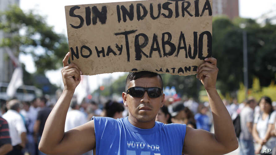 """A demonstrator holds a sign that reads in Spanish """"Without industry there is no work"""" during a labor march in Buenos Aires, Tuesday, March 7, 2017."""
