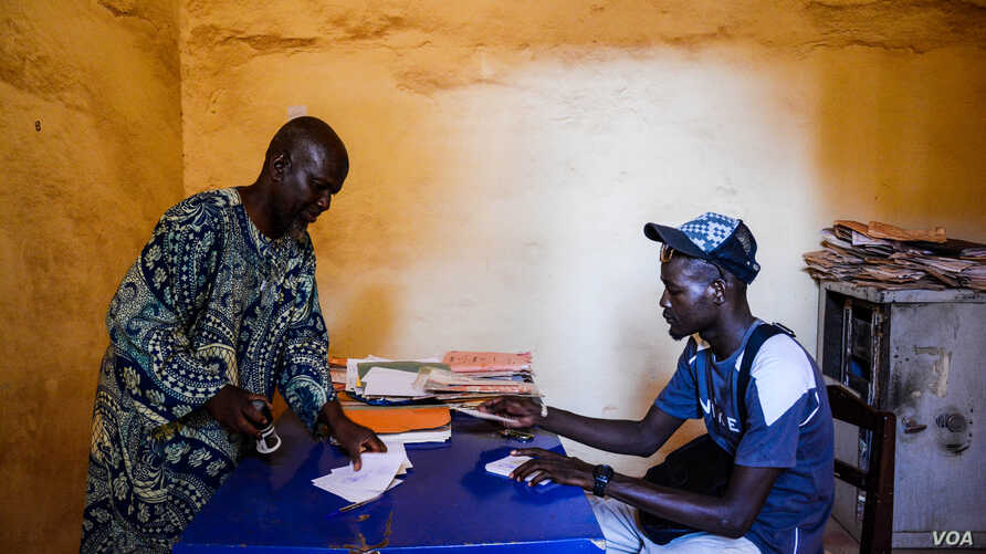 The director of Timbuktu's post office, Ousmane Aliou Maiga, together with Ali Nialy, a guide and Timbuktu resident. After launching the postcard project Nialy quickly Maiga's best client. (K. Höije/VOA)