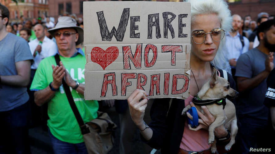 A woman holds a placard as they take part in a vigil for the victims of an attack on concert goers at Manchester Arena, in central Manchester, Britain, May 23, 2017.