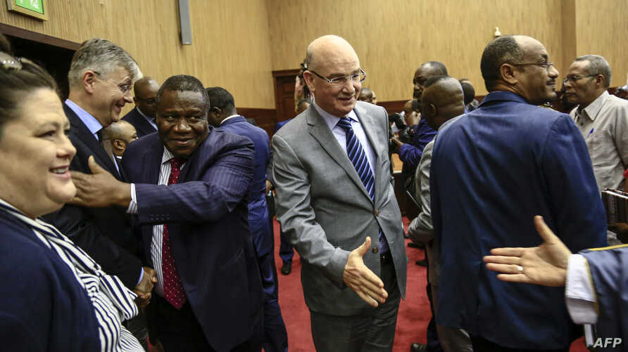 FILE - Jean-Pierre Lacroix, second left, the U.N. undersecretary-general for peacekeeping operations, and Smail Chergui, center, the African Union's commissioner for peace and security, shake hands with delegates after the inaugural session of peace