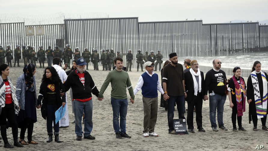 People hold hands in prayer during a protest in San Diego, near the border with Tijuana, Mexico, Dec. 10, 2018.