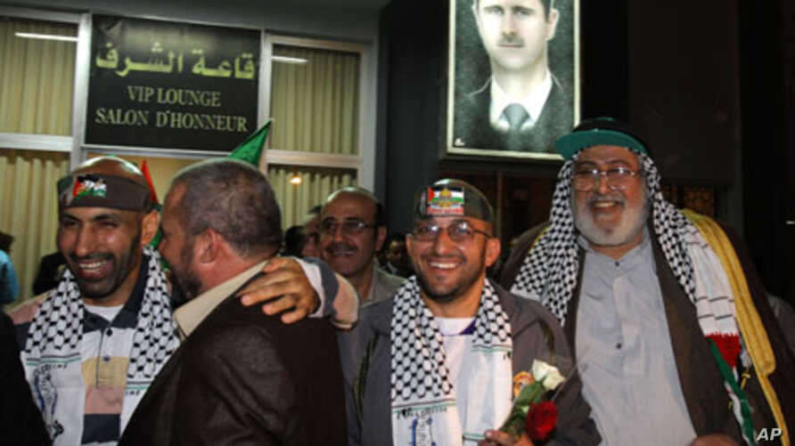 Some of the 16 Palestinian prisoners  smile as they arrive at the airport in Damascus, Syria early on October 19, 2011.