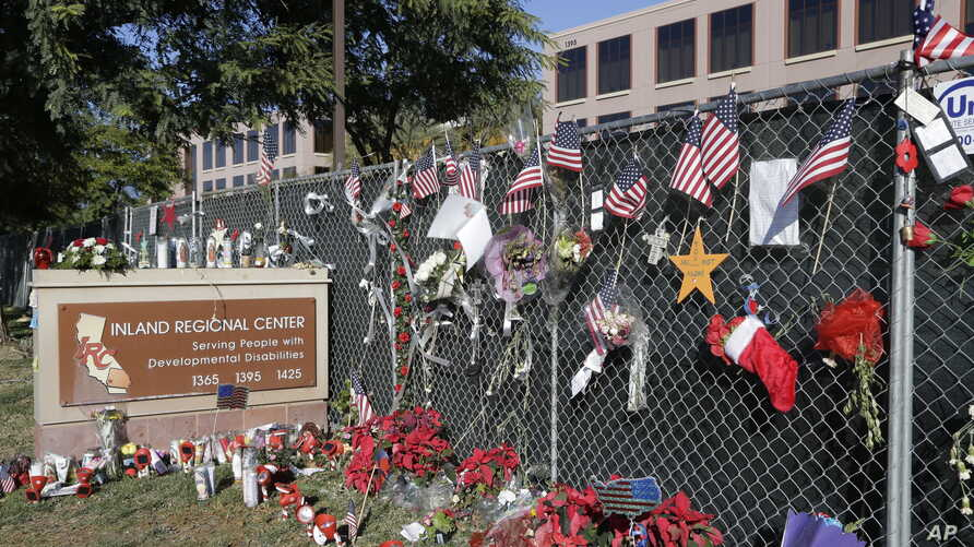 FILE - Flowers and American flags honoring the victims of the Dec. 2, 2015, terror attack at the Inland Regional Center are seen outside the complex in San Bernardino, California, Dec. 29, 2015.