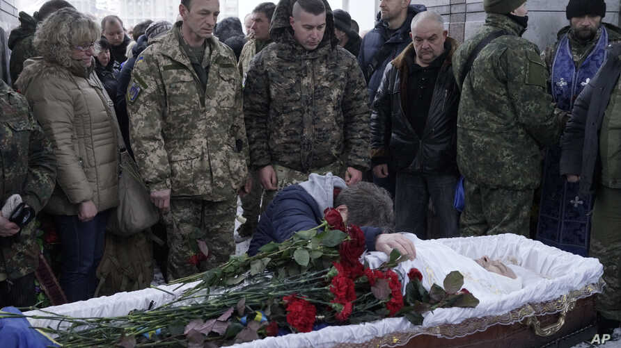 Fellow Ukrainian government soldiers and mourners bid farewell to Oleksandr Ilnitsky, who was shot dead by a pro-Russian rebel sniper in Ukraine's eastern Donetsk region, during a service in Kyiv's Independence Square, Jan. 11, 2016.