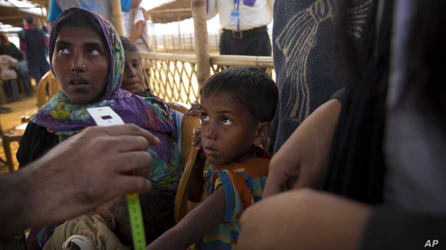 A newly arrived Rohingya Muslim boy looks as a UNHCR volunteer takes the measurement after their arrival at the transit camp at Balukhali refugee camp 50 kilometres (32 miles) from Cox's Bazar, Bangladesh, Sunday, Jan. 14, 2018.