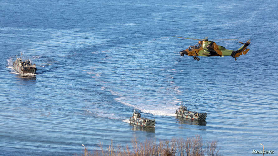 Landing craft and a helicopter are seen during NATO's Exercise Trident Juncture, off the Trondheim coast, Norway, Oct. 30, 2018.