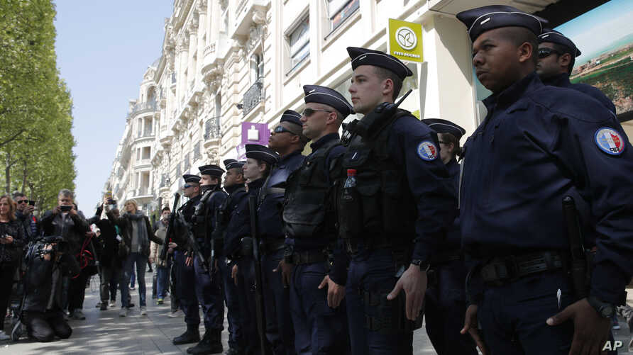 A dozen of police officers stand at attention at the place where a police officer was killed Thursday on the Champs Elysees boulevard, April 21, 2017 in Paris.