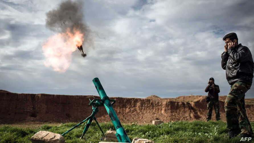 Syrian rebels fire a mortar towards regime forces stationed at Kwiriss airport in Al-Bab, 30 kilometers from the northeastern Syrian city of Aleppo, February 14, 2013.