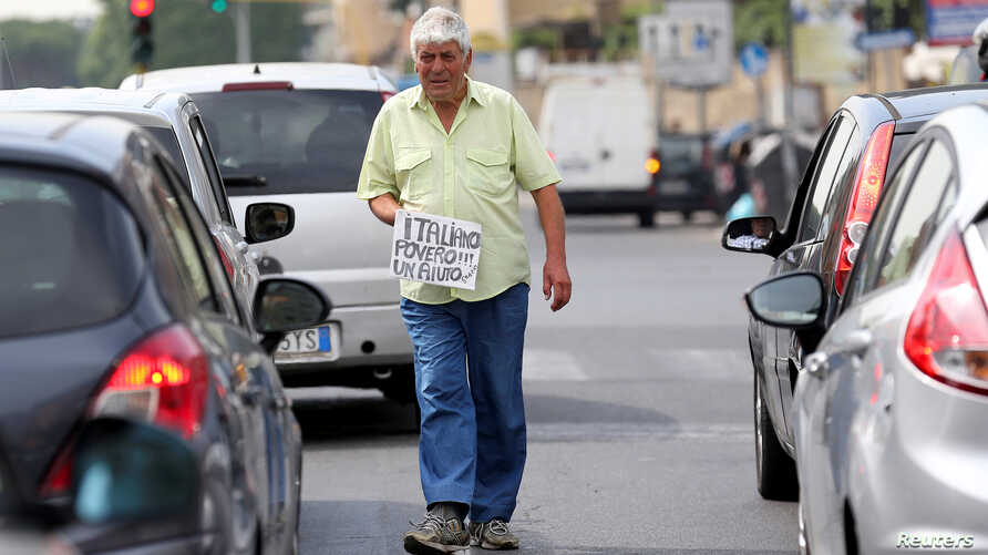 "An Italian man walks between cars as he holds a banner reading ""I'm a poor Italian, help me, thanks"" in Rome, May 28, 2018."