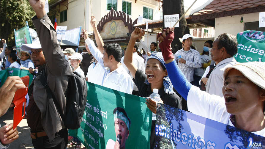 Protesters raise clenched fists with banners printed with detained activist Vorn Pao in front of the Appeals Court during a rally in Phnom Penh, Cambodia, March 24, 2014.