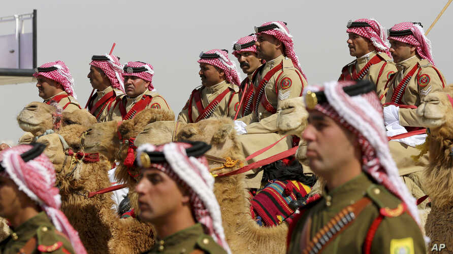 An honor guard on camelback greets Saudi Arabia's King Salman, not seen, in a lavish welcome ceremony complete with cannon salutes, in Amman, Jordan, March 27, 2017. Salman is in Jordan to attend the annual Arab Summit, to be held March 29.