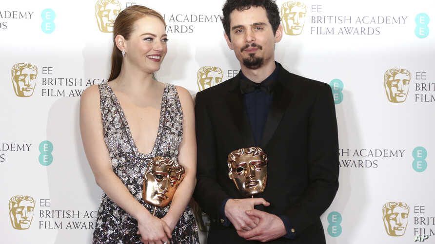 """Actress Emma Stone with her BAFTA award for Best Actress and director Damien Chazelle with his BAFTA award for Best Director both for the film """"La La Land' pose backstage at the British Academy Film Awards in London, Sunday, Feb. 12, 2017."""