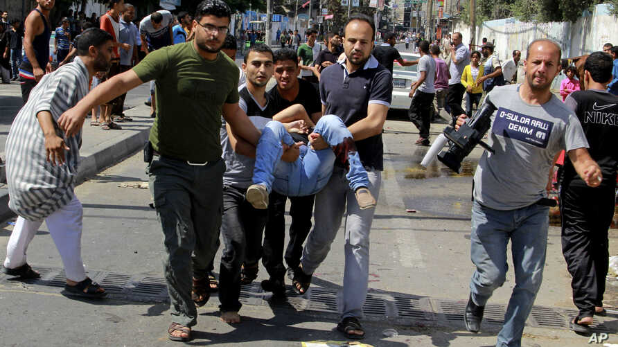 Palestinians carry a person killed in a blast outside a UN run school in Rafah, in the southern Gaza Strip, Sunday, Aug. 3, 2014.