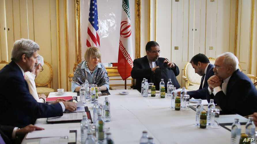 U.S. Secretary of State John Kerry, second from left, Iranian Foreign Minister Mohammad Javad Zarif, second from right, meets at a hotel in Vienna, June 27, 2015.