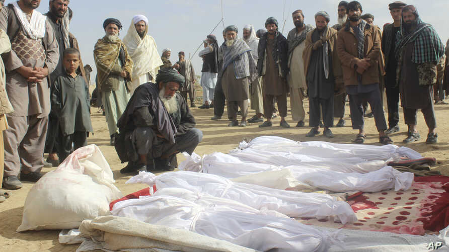 Afghan villagers gather around several victims' bodies who were killed during clashes between Taliban and Afghan security forces in Taliban's controlled village, Buz-e Kandahari village in Kunduz province, north of Kabul, Afghanistan, Friday, Nov. 4,...
