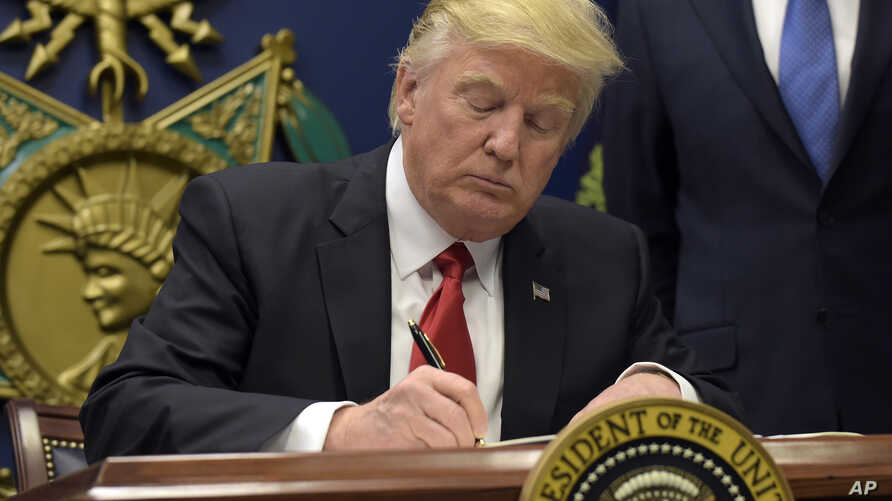 President Donald Trump signs an executive order on extreme vetting during an event at the Pentagon in Washington, Jan. 27, 2017.