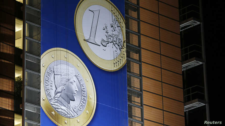 A banner showing a Latvian Euro coin is seen on the facade of the European Commission headquarters during a European Union leaders summit in Brussels December 20, 2013. Latvia will join the euro zone on Jan. 1, 2014.