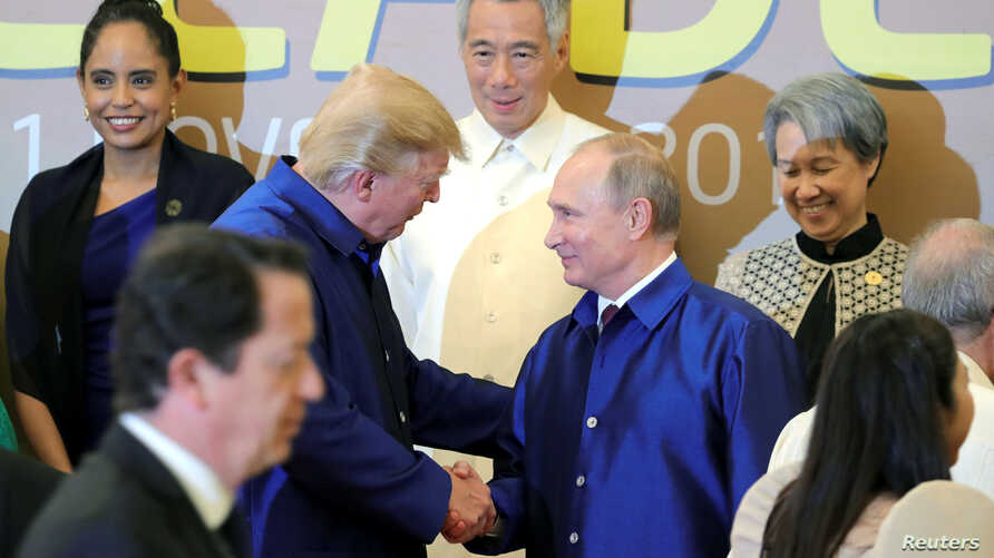 U.S. President Donald Trump and Russian President Vladimir Putin shake hands as they take part in a family photo at the APEC summit in Danang, Vietnam, Nov. 10, 2017.