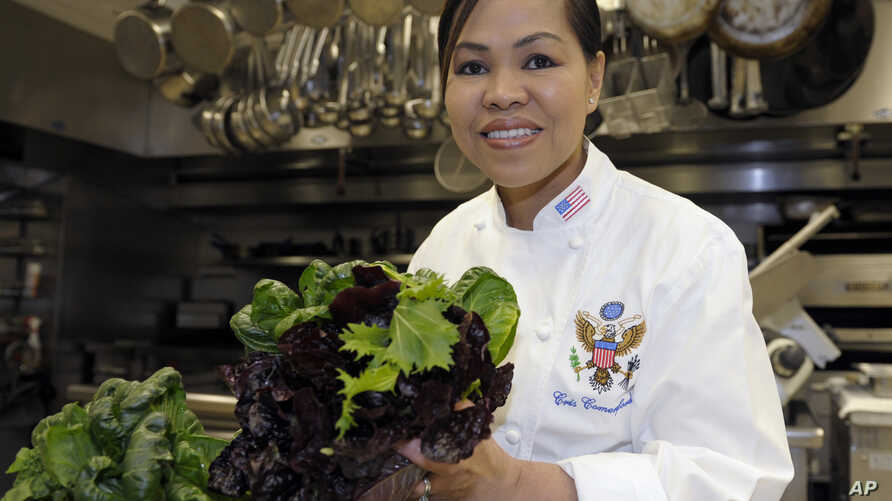 FILE - White House chef Cristeta Comerford holds produce in the kitchen of the White House in Washington.