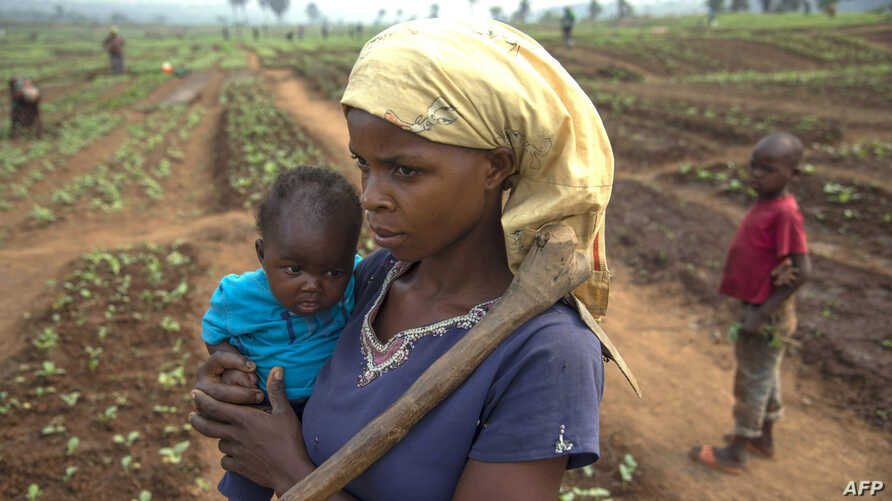 FILE - A woman and her child, who fled from rebel attacks, stand in a field, in Tshikapa, Kasai Region, Democratic Republic of Congo, July 27, 2017.