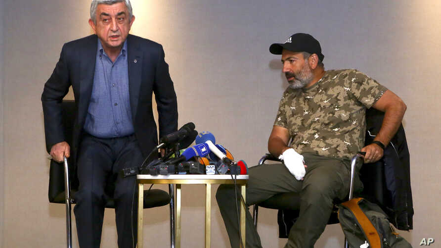 Former Armenian President Serzh Sargsyan (L) walks out of a meeting with protest leader Nikol Pashinian (R) in Yerevan, Armenia, April 22, 2018.