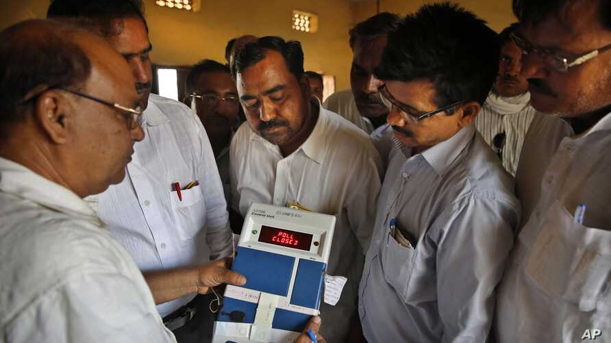 Indian election officials seal an electronic voting machine after the closing of a polling center in Kunwarpur village, Uttar Pradesh state, India, May 12, 2014.