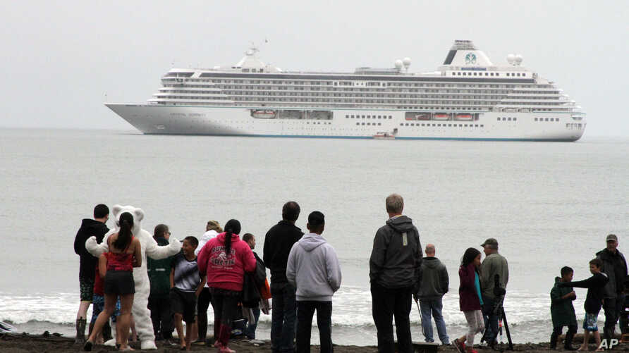 Historic Arctic Cruise: This Aug. 21, 2016, photo shows people preparing to take a polar plunge in the Bering Sea in front of the luxury cruise ship Crystal Serenity, which anchored just outside Nome, Alaska. The ship made a port call as it became th