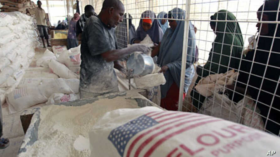 Newly arrived Somali refugee women receive relief food at a the World Food Program distribution center at the Ifo refugee camp in Dadaab, near the Kenya-Somalia border, August 1, 2011