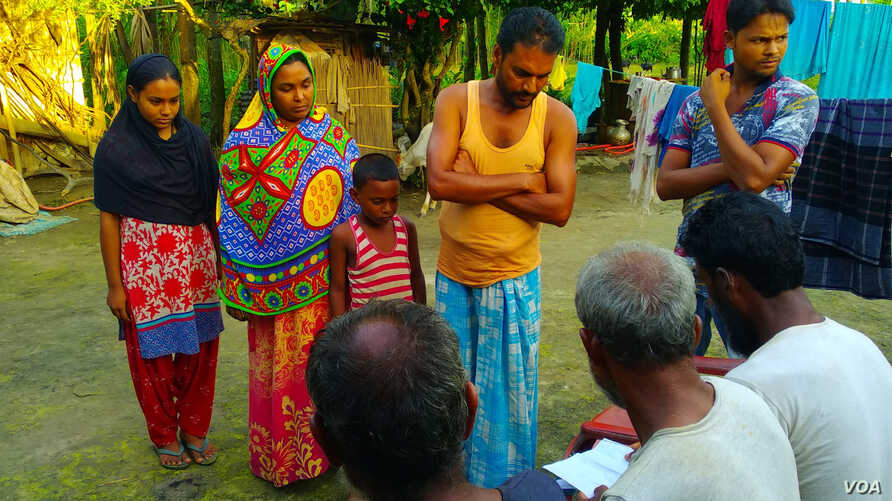 Osman Goni, with his wife and two children, showing some villagers the copies of some of the documents he had submitted to the authorities last year, seeking inclusion to the NRC of all members of his extended family, Aug. 2, 2018. When the NRC draft