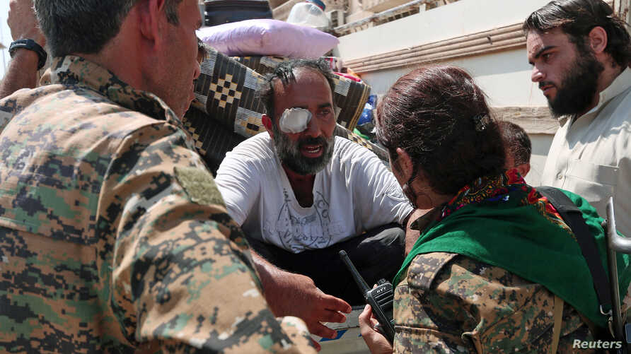 Syria Democratic Forces fighters chat with an injured civilian who was evacuated with others by the SDF from an Islamic State-controlled neighborhood of Manbij, in Aleppo Governorate, Syria, Aug. 12, 2016. The SDF has said Islamic State was using civ