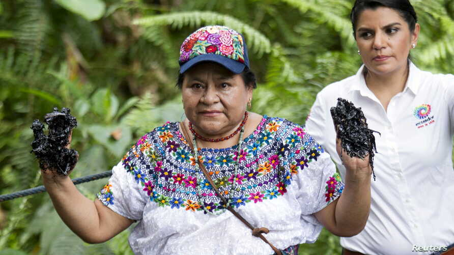 FILE - Guatemalan indigenous rights activist and Nobel Peace Prize winner Rigoberta Menchu shows her hands covered with oil at the Aguarico 4 oil well in Shushufindi June 3, 2015. Menchu visited the oil well, located in Ecuador's Amazon region Lago A