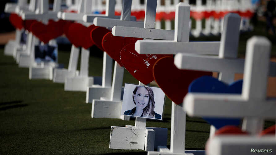 A photograph hangs from one of the 58 white crosses set up for the victims of the Route 91 music festival mass shooting in Las Vegas, Nevada, Oct. 5, 2017.