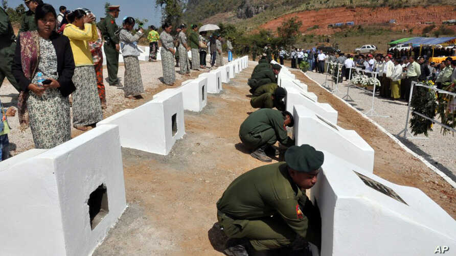 In this photo released by the Myanmar Defense Ministry, soldiers place urns containing ashes of soldiers fallen during a recent fighting against ethnic Kokang rebels at a military funeral in Lashio, Myanmar,In this Monday, Feb. 23, 2015.