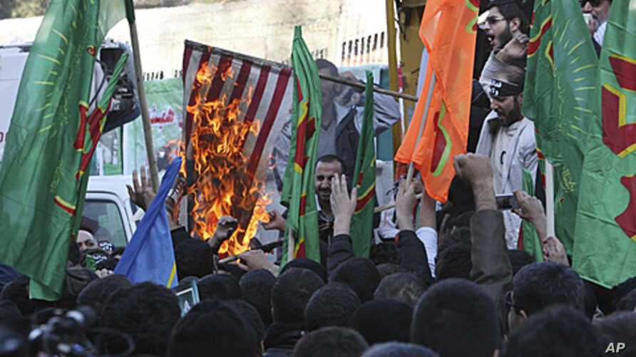 Iranian demonstrators, burn a US flag, in an annual state-backed rally in front of the former US Embassy in Tehran, Iran marking the anniversary of the seizure of the US Embassy by militant students, November 4, 2011.