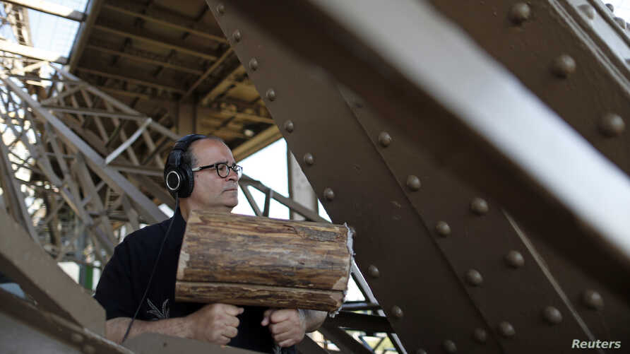 U.S. composer Joseph Bertolozzi makes sounds by striking the surface of the Eiffel Tower with a large log wrapped in lambswool for a musical project called 'Tower Music' in Paris, June 7, 2013.