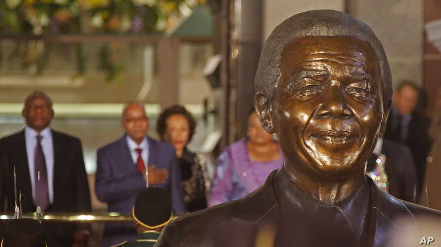South African President Jacob Zuma, second left, in background with a bust of former South African President Nelson Mandela, center, outside Parliament before giving the State of the Nation address in the city of Cape Town, South Africa, June 17, 201...