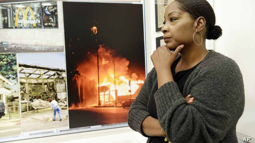 """Katynja McCory, lead docent for the """"Re-Imagine Justice"""" art exhibit, looks at L.A. Riots photos featured in the exhibit at the Community Coalition, April 18, 2017. When she thinks back to the Rodney King riots, McCory recalls that her mother told th"""