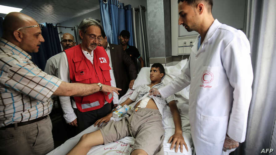 FILE - Francesco Rocca (2nd-L), the President of the International Federation of Red Cross and Red Crescent Societies, meets a Palestinian receiving treatment for wounds sustained during protests at the Gaza-Israel boder, during his tour of the Red C