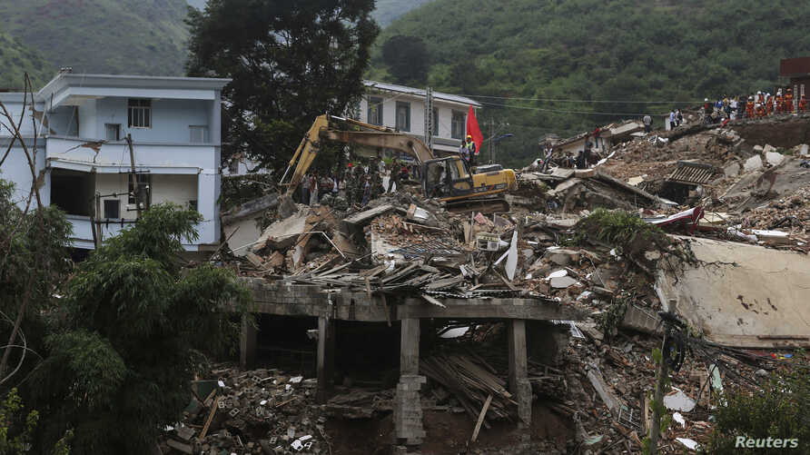 An excavator moves debris to search for bodies of quake victims in Zhaotong, Ludian county, Yunnan province, China, August 5, 2014.