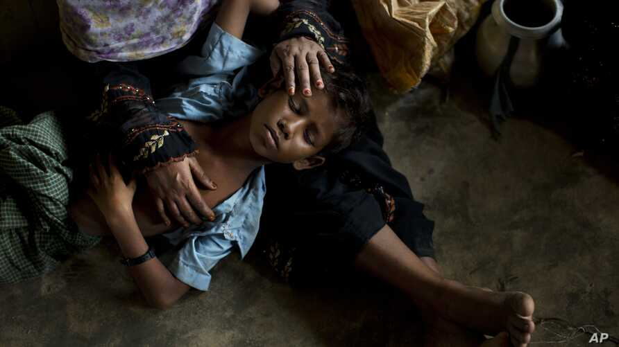 A Rohingya woman comforts her exhausted son as they take shelter inside a school after having just arrived from the Myanmar side of the border at Kutupalong refugee camp, Bangladesh, Sept. 7, 2017.