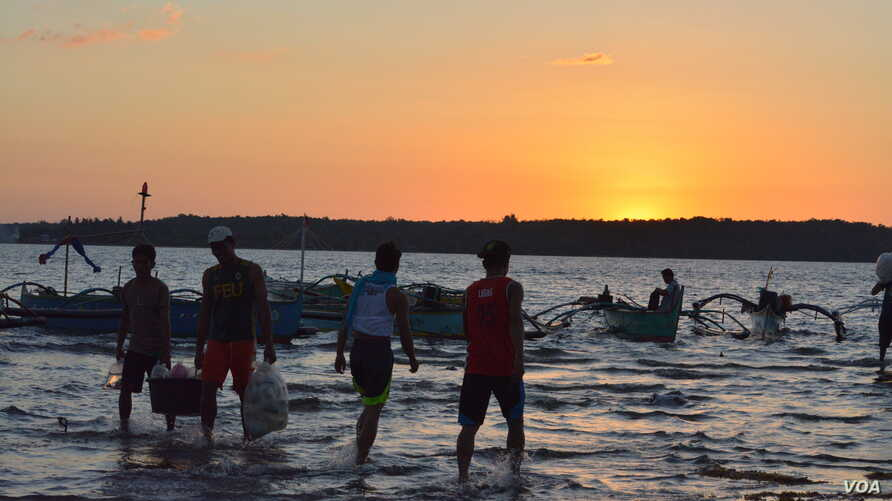 At sunset on the shores of Masinloc town fishermen return from a day of fishing nearby in the South China Sea, while others head out for overnight fishing, Masinloc, Philippines, Nov. 8, 2015.  (S. Orendain/VOA)