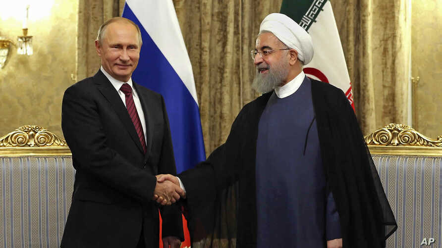 FILE - In this Nov. 1, 2017 file photo released by an official website of the office of the Iranian Presidency, Iran's President Hassan Rouhani, right, shakes hands with Russian President Vladimir Putin, at the Saadabad Palace in Tehran.