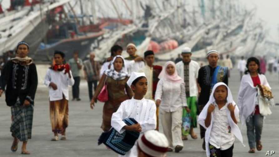 Indonesian Muslims walk to attend Eid al-Fitr prayers that marks the end of the holy fasting month of Ramadan at Sunda Kelapa port in Jakarta, Indonesia, August 31, 2011