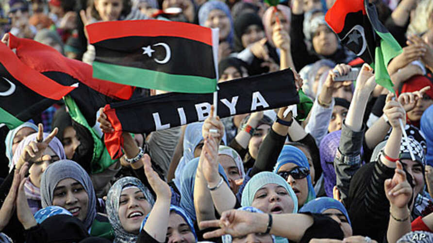 Libyans wave their new national flag as they celebrate following the official declaration of liberation of the entire country, October 23, 2011.