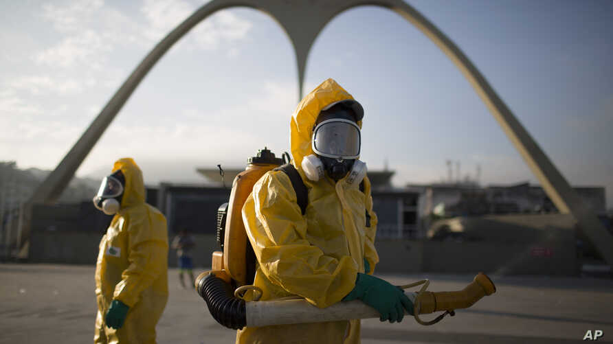 FILE - In this Tuesday, Jan. 26, 2016, photo, a health workers stands in the Sambadrome spraying insecticide to combat the Aedes aegypti mosquito that transmits the Zika virus in Rio de Janeiro, Brazil. The Sambadrome will be used for the Archery com